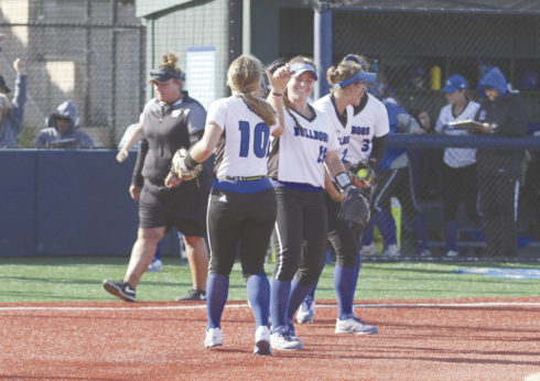 CSM's LaurenQuirke is high fived by first baseman LexiRiccardi after the Bulldogs captured the Coast Conference title with a 9-6 win over rival Ohlone. Photo by Nathan Mollat/Daily Journal