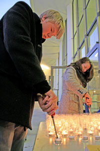 Heather Murtagh/Daily Journal Max Peterson, left, the son of a part-time teacher at the College of San Mateo, and part-time English teacher Rebecca Webb light candles for a vigil supporting education held on campus last night.