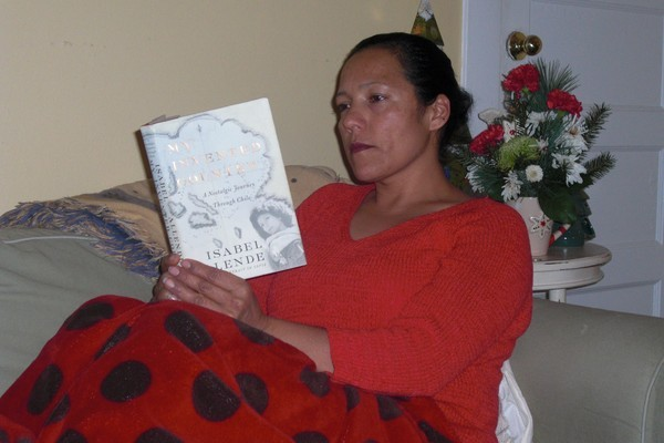 Ninfa Patino reading a book by one of her favorite writers, Isabel Allende.