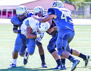 CSMreceiver Johnny Niupalu is brought down by a host of Delta defenders in Saturday's 43-30 loss. Photo by Patrick Nguyen