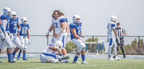 College of San Mateo linebacker Laipeli Palu, right, celebrates after making a stop on third-and-goal against Modesto on the Bulldogs' first defensive series of the season Saturday at College Heights Stadium. Photo by Patrick Nguyen.