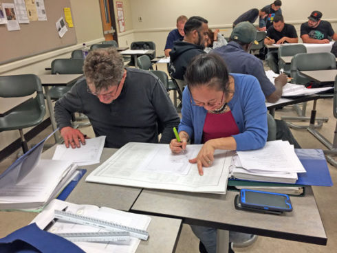 Dawn Togami, right, learns how to read construction blueprints in the Trades Introduction Program, aimed at helping those interested in the trades prepare for apprenticeship programs. Photo by Courtesy of the Trades Introduction Program.