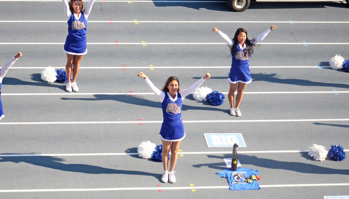 Joyce Khoury cheers beside a tribute to former College of San Mateo cheerleader Anjela Soto Sunday.