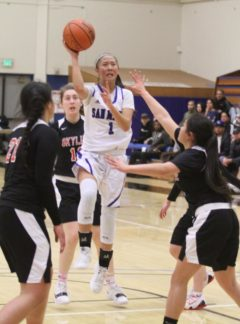CSM's Ava Agustin splits a pair of Skyline defenders on her way to the basket. Photo by Nathan Mollat/Daily Journal.