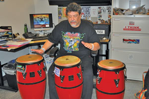 Kerry Chan/Daily Journal Rudy Ramirez, ethnic studies professor at the College of San Mateo, plays music in his office. He will be presenting a history of Latin rock and its impact on society Wednesday at the college. The Mission Street All-Stars will also be playing live.