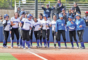CSM's Lelani Akai is greeted by her teammates as she jumps on home plate in celebration of her third-inning home run. The Lady Bulldogs went on to a 20-0 rout of Foothill to finish their historic undefeated season with a 35-0 record. Photo by: Terry Bernal/Daily Journal