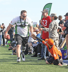 Wounded Warrior Amputee Football Team co-captain BJ Ganem slaps hands with a young fan after a touchdown Saturday at the College of San Mateo. Photo by Terry Bernal/Daily Journal.